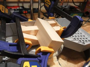 The 4-inch long block of wood, held by the two jig pieces.